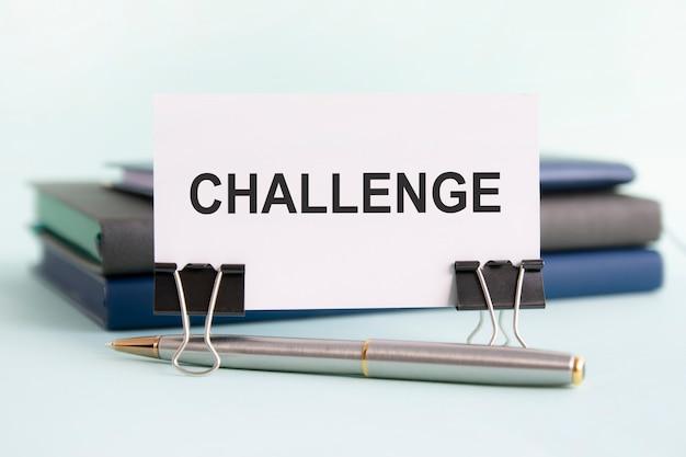 Um cartão branco com o texto do desafio é colocado em clipes de papel em uma mesa contra o fundo azul claro, com foco seletivo