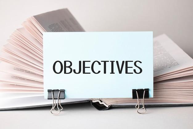 Um cartão branco com o texto objetivos fica em um clipe para papéis na mesa contra um livro