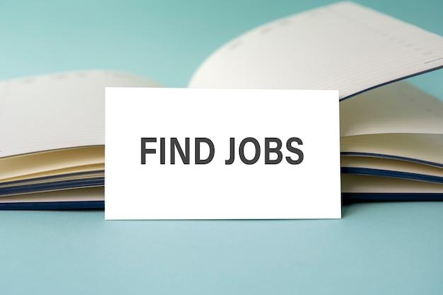 Um cartão de visita branco com o texto find jobs está em uma mesa contra o fundo de um diário aberto. desfocado.