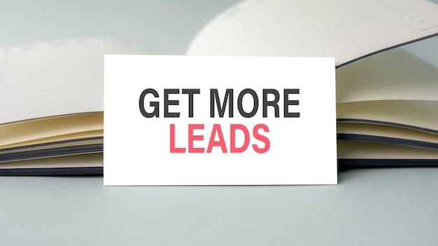 Um cartão de visita branco com texto get more leads está em uma mesa no contexto de um diário aberto. desfocado