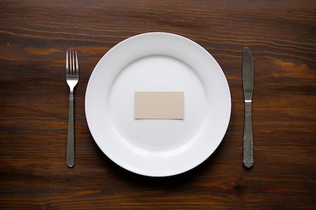 Um cartão de visita ou uma folha de papel em branco em um prato branco vazio