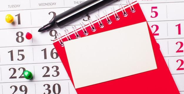 Um cartão em branco para inserir texto ou ilustrações encontra-se no calendário. perto está um bloco de notas vermelho e um marcador. vista de cima