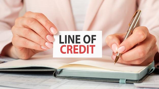 Um cartão na mão de uma mulher com a linha de crédito de inscrição