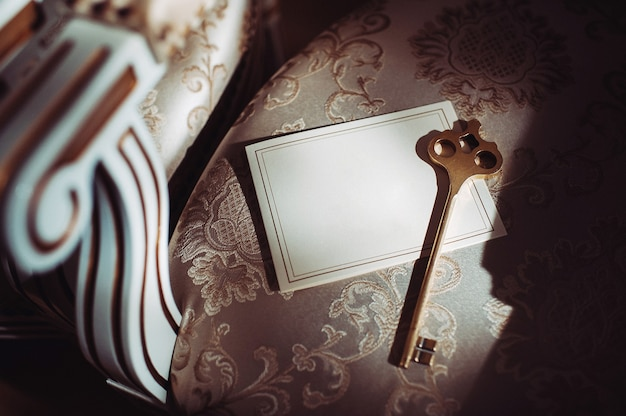 Um cartão postal e uma chave velha no fundo de uma velha cadeira natural.