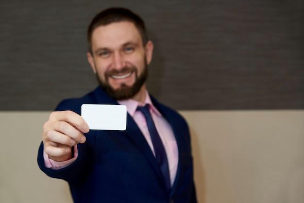 Um cartão vazio branco nas mãos de um homem de barba turva