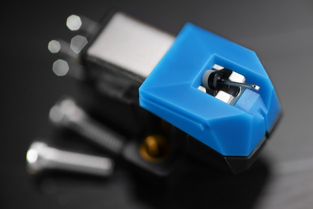 Um cartucho de bobina móvel de fonógrafo magnético em disco de vinil. foto macro.