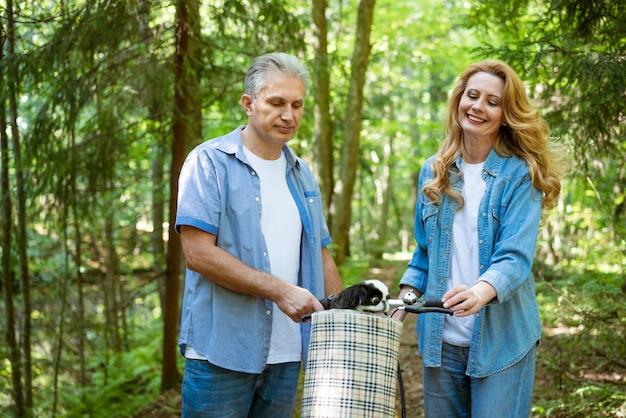 Um casal adulto em roupas de brim passeando na floresta com um cachorro sentado na cesta de uma bicicleta