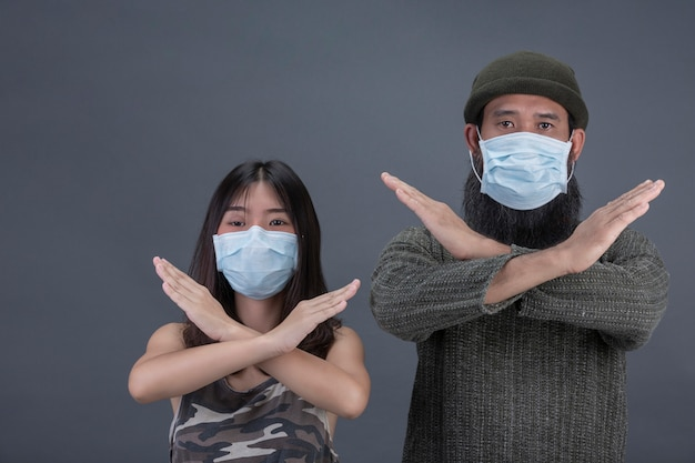 Um casal amor está usando máscara ao fazer parar a mão na parede preta.