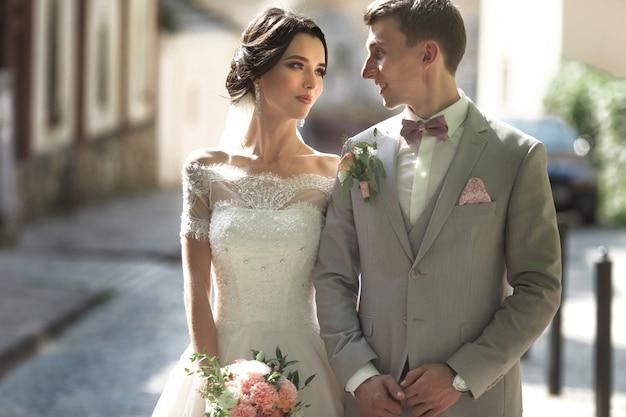 Um casal amoroso de recém-casados caminha pela cidade e sorri,