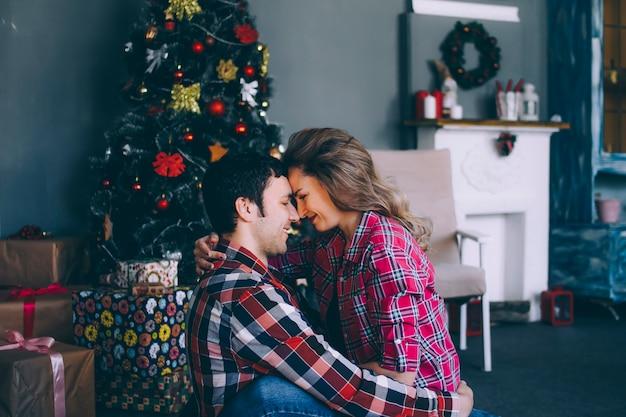 Um casal amoroso marido e mulher, abraçando-se debaixo da árvore do ano novo.