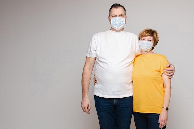 Um casal apaixonado abraça e fica em máscaras médicas
