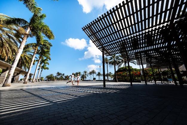 Um casal apaixonado atravessa uma praça em san sebastian de la gomera, nas ilhas canárias, espanha