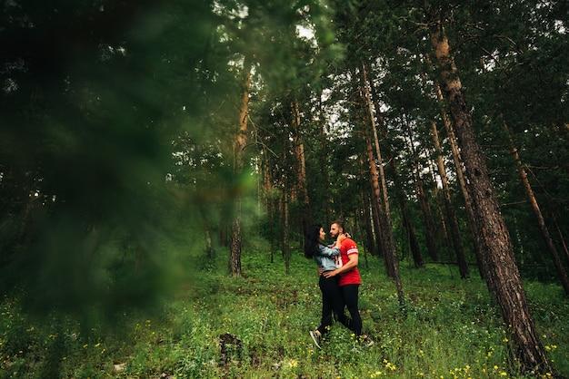 Um casal apaixonado caminha pela floresta de coníferas. cara e menina abraçando na floresta.