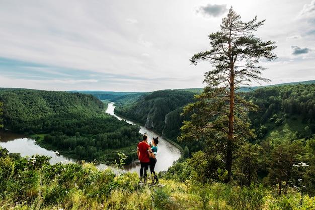 Um casal apaixonado caminha pela floresta de coníferas. homem e mulher em uma viagem de acampamento.