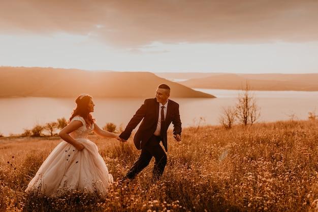 Um casal apaixonado de noivos noivos em um vestido branco e um terno anda, corre e sorri feliz na grama alta no campo de verão na montanha acima do rio