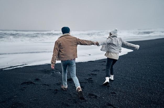 Um casal apaixonado de turistas de mãos dadas se diverte enquanto caminha pela praia de areia vulcânica negra e admira as grandes ondas do mar.