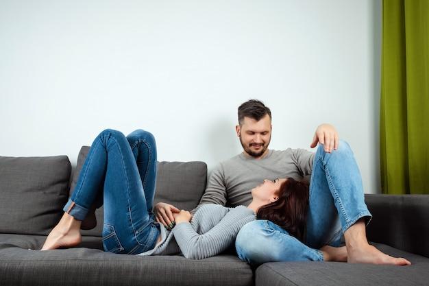 Um casal apaixonado deitado em uma cama em casa