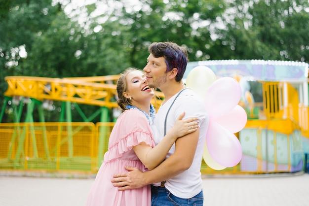 Um casal apaixonado em roupas brilhantes se abraçam, uma garota segura balões nas mãos, sorriem e estão felizes