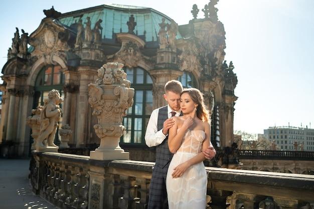 Um casal apaixonado em um casamento anda no famoso palácio barroco zwinger em dresden, saxônia, alemanha.