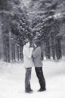 Um casal apaixonado em uma caminhada de inverno. homem e mulher em um encontro no parque no inverno. amigos em um parque de inverno