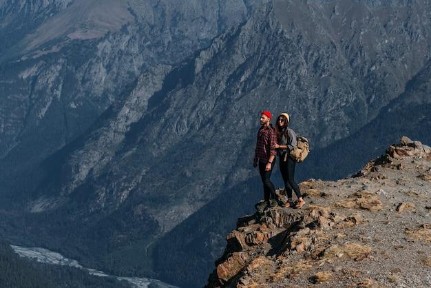 Um casal apaixonado em uma rocha admira as belas paisagens. um homem e uma mulher em uma rocha. um casal apaixonado viaja. um homem e uma mulher nas montanhas do cáucaso. casal viajando pelas montanhas