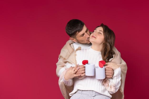 Um casal apaixonado, envolto em um cobertor quente, segura xícaras de chá quente. fundo vermelho.
