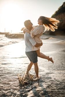 Um casal apaixonado está caminhando na praia perto do mar. família jovem ao pôr do sol à beira-mar do mar mediterrâneo. conceito de férias de verão