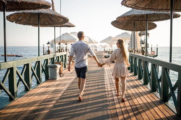 Um casal apaixonado está descansando à beira-mar na turquia. homem e mulher no cais. passeio marítimo. lua de mel. casal em viagem de lua de mel. um lindo casal viaja pelo mundo. casal feliz de férias.
