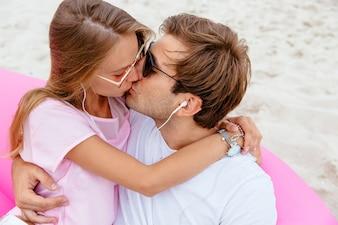 Um casal apaixonado está se beijando, enquanto ouve música em fones de ouvido, sentado no sofá de ar