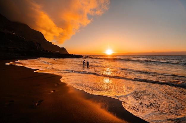 Um casal apaixonado fica no oceano à noite, olhando o belo pôr do sol na ilha de tenerife. espanha.