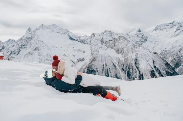 Um casal apaixonado no inverno na neve. beijo na neve nas montanhas.