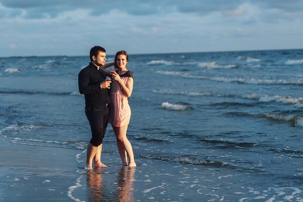 Um casal apaixonado passeia à noite à beira-mar