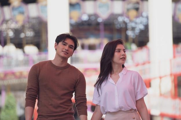 Um casal apaixonado por uma jovem mulher engraçada e feliz e um homem andando ou correndo no fundo do parque de diversões.