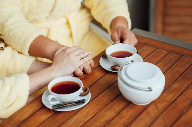 Um casal apaixonado se senta em roupão e bebe chá em uma mesa de madeira