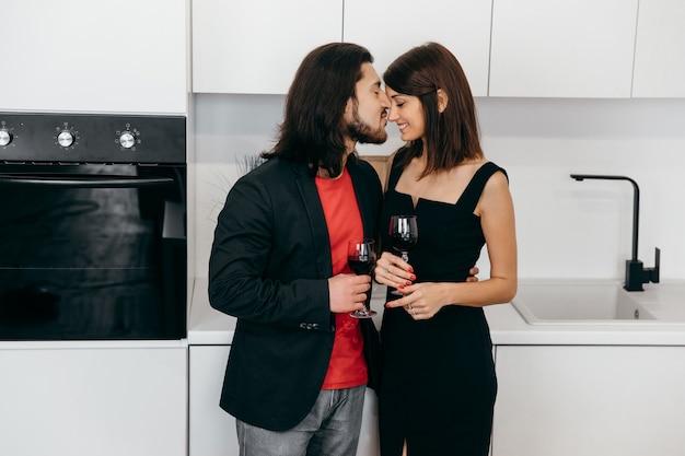 Um casal apaixonado segurando taças de vinho nas mãos e se beijando ternamente em casa