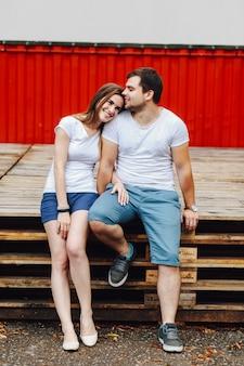 Um casal apaixonado, sentado em paletes contra uma cena vermelha no verão