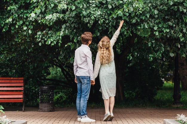 Um casal apaixonado, uma jovem garota e um homem, de pé no parque, abraços, encontro, beijos, buquê