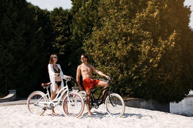 Um casal aproveitando um dia na praia andando de bicicleta em tandem.