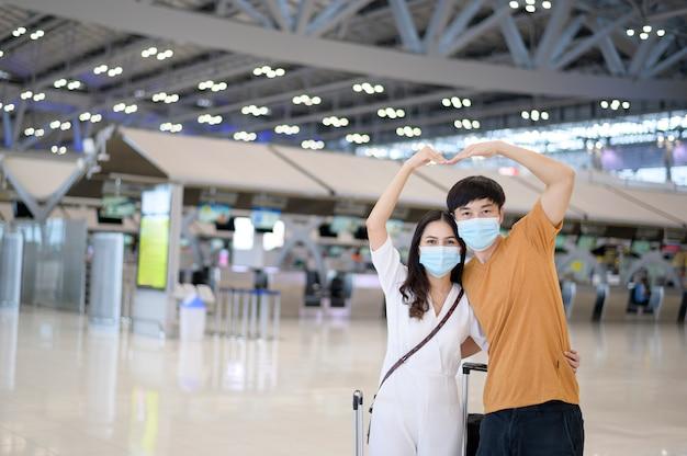 Um casal asiático está usando máscara protetora no aeroporto internacional, viajando sob a pandemia de covid-19,