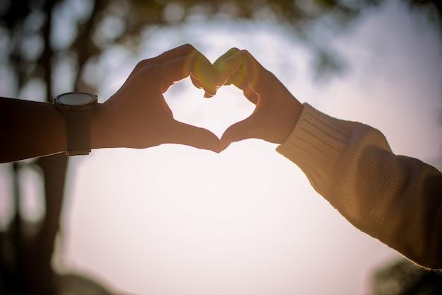 Um casal asiático faz formato de coração das mãos deles.