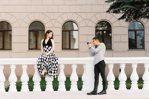 Um casal bonito e elegante de futuros pais está andando pela cidade
