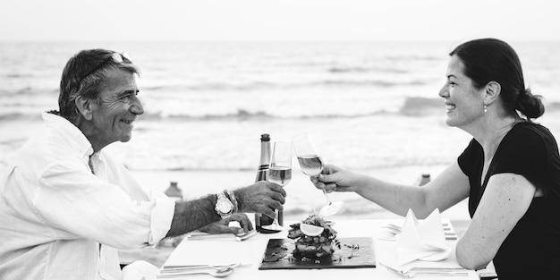 Um casal brindando na praia