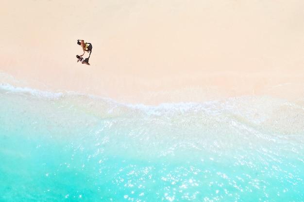 Um casal caminha ao longo da praia das maurícias, no oceano índico.