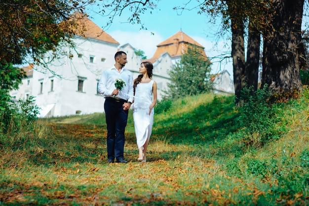Um casal caminha em um parque de outono perto do castelo. casado agora mesmo.