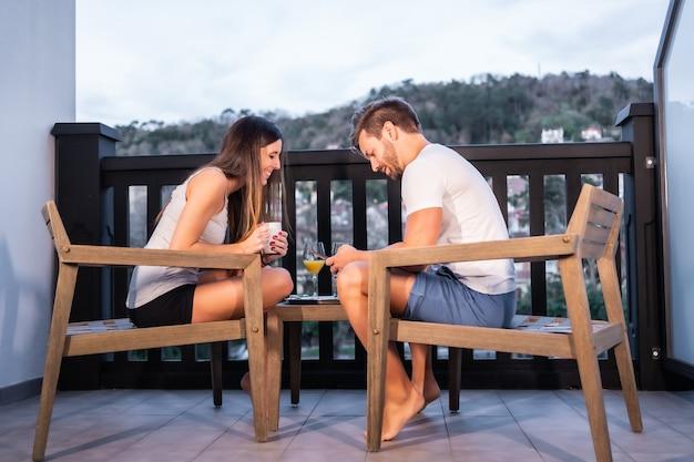 Um casal caucasiano tomando café da manhã no terraço do hotel de pijama. brindando com suco de laranja pela manhã, estilo de vida de um casal apaixonado