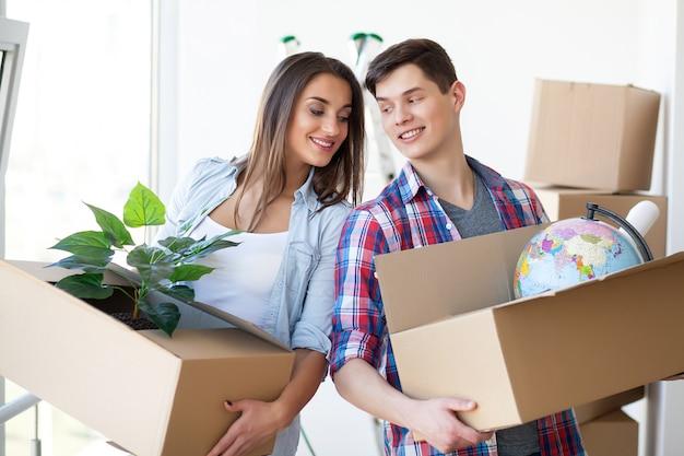 Um casal com caixas se muda para uma nova casa,