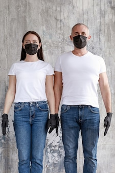 Um casal com máscaras pretas e luvas de borracha pretas