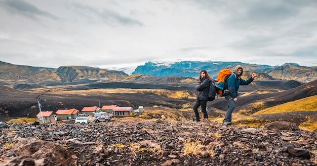 Um casal com mochilas saindo do abrigo da caminhada de 54 km de landmannalaugar, islândia