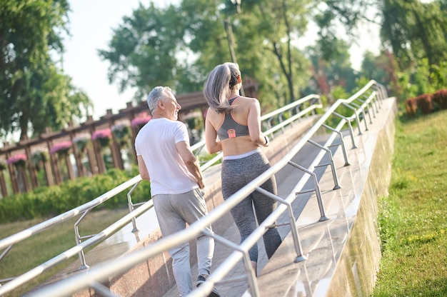 Um casal correndo no parque pela manhã
