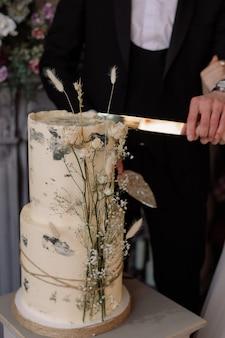 Um casal corta um lindo bolo de beliche decorado com flores secas